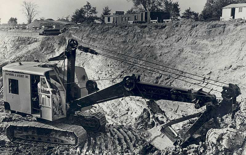 An early photo of a Raymond J. Avent crane digging at a contruction site.